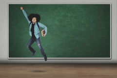 Afro man jumping with book in classroom Royalty Free Stock Image