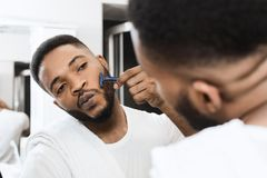 Beard care concept. Afro man shaving his beard looking in mirror at bathroom. Beard care concept stock photo