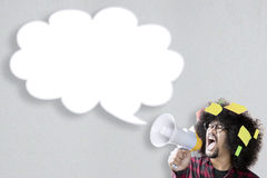 Afro man shouting at empty speech bubble. Young Afro man with curly hair, shouting at empty cloud speech bubble through a megaphone with post it on his hair Royalty Free Stock Photo