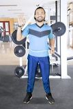 Afro man showing OK sign for his waist. Portrait of young Afro man measuring his waist while showing OK sign and standing in the gym center Royalty Free Stock Photo