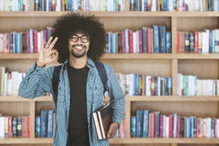 Afro man showing ok sign in library. Handsome afro man showing ok sign while holding book and standing in the library royalty free stock image