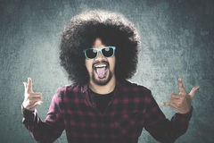 Afro man with silly gesture. Portrait of Afro man with curly hair, wearing sunglasses and showing silly gesture. Shot with a wall background Royalty Free Stock Images