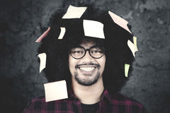 Afro man with sticky note on hair. Close up of a young Afro man with casual clothes, smiling at the camera while wearing glasses with sticky note on his curly Stock Photos