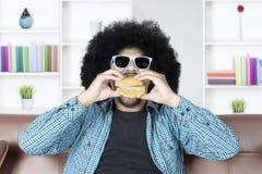 Afro man with sunglasses eats burger Stock Photos