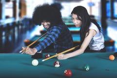 Afro man teaches his friend to play billiard Stock Photo