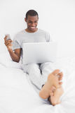 Afro man text messaging while using laptop in bed Royalty Free Stock Photos