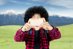Afro man using a smartphone for take pictures Stock Image