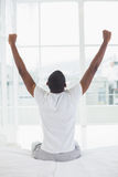 Afro man waking up in bed and stretching his arms stock photography
