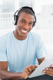 Afro man wearing headphones while using digital tablet Stock Photography