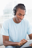 Afro man wearing headphones while using digital tablet on sofa Stock Photos