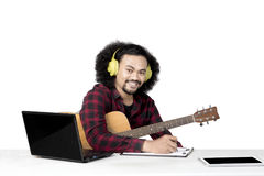 Afro musician composes a song. Image of an afro musician holding a guitar while composing a song in the studio, isolated on white background Royalty Free Stock Photography