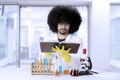 Afro naukowiec czyta podręcznika Obraz Stock