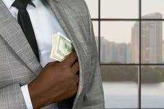 Afro office executive hiding money. Stock Photos