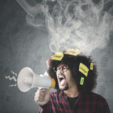 Afro person with help text and megaphone. Young Afro person looks stressful, shouting through a megaphone with help texts and smoke on his curly hair Stock Photography