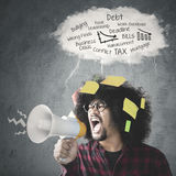 Afro person with megaphone. Young Afro person looks angry and shouting through a megaphone with paper notes attached on his hair, shot under a speech bubble of Stock Photo
