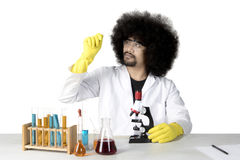 Afro scientist looking at a microscope slide. Image of an Afro male scientist looking at a microscope slide while doing chemical research, isolated on white Royalty Free Stock Photography