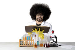 Afro scientist reading a book on studio. Picture of an Afro male scientist reading a book while doing chemical research, isolated on white background Royalty Free Stock Photography