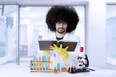 Afro scientist reading a textbook. Portrait of Afro scientist reading a textbook and sitting in the laboratory Stock Image