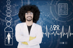 Afro scientist smiling at camera. While standing with crossed arms. Shot with virtual screen background Stock Photo