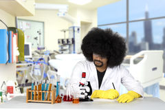 Afro scientist writes observation report. Afro scientist writing observation report while doing experiment in the laboratory Stock Photos
