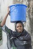 Afro- skönhet som bär en hink av vatten i en kula Arkivbild