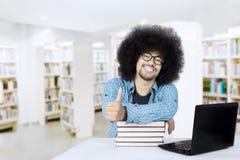 Afro studencki pokazuje kciuk up w bibliotece Obrazy Royalty Free
