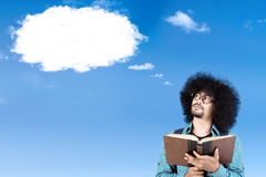 Afro student with book and a speech bubble. Afro college student reading a book while looking at a cloud speech bubble on the sky Royalty Free Stock Images