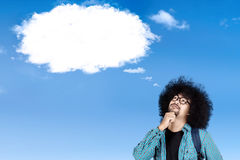 Afro student with cloud speech bubble. Afro college student thinking an idea while looking at empty cloud speech bubble on the sky Stock Photography