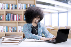 Afro student with earphone in the classroom. Picture of Afro college student learning with a laptop and books while using a earphone in the classroom Stock Image