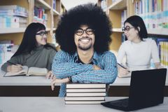 Afro student with his friends in the library. Afro male student smiling at the camera while studying with his friends in the library Royalty Free Stock Image