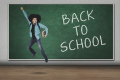 Student jumping with back to school text. Afro student holding book while jumping with back to school text on chalkboard Royalty Free Stock Image