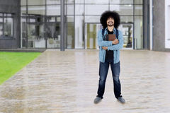 Afro student holds book at school. Full length of a male Afro student holding a book and smiling at the camera while standing at the school yard Stock Photography