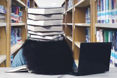 Afro student looks exhausted at library. Portrait of Afro male student looks exhausted with stack of books over his head while sleeping in the library Royalty Free Stock Photos
