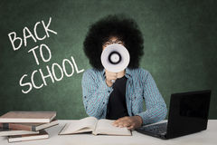 Afro student shouting by using a megaphone. Afro college student shouting by using a megaphone while sitting with word of back to school on the chalkboard Stock Photos