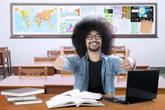 Afro student show thumbs up in the classroom. Image of an Afro college student is learning with a laptop and books while showing thumbs up in the classroom Stock Image