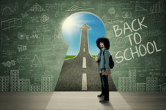 Afro student shows thumb up on keyhole. Male Afro student showing thumb up in front of a keyhole with text of Back to School and upward arrow Royalty Free Stock Image
