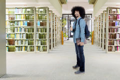 Afro student shows thumb up in library. Male Afro student standing in the library while carrying bag and showing thumb up Stock Photo