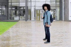Afro student shows thumb up at school. Full length of a male Afro student standing at school yard while showing thumb up and holding books Royalty Free Stock Image