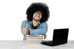 Afro student shows thumb up on studio. Photo of an Afro male college student showing thumb up while studying with a laptop and books on the desk Royalty Free Stock Photo