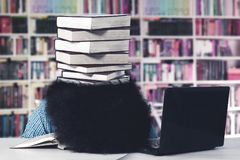 Afro student sleeping with a stack of books. Picture of an Afro male college student sleeping in the library with a stack of books on his head Royalty Free Stock Photography