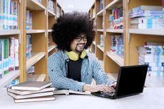Afro student studying in the library. Portrait of Afro male student is studying with a laptop and books on the table while sitting in the library Royalty Free Stock Photography