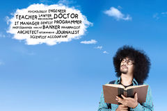 Afro student thinking his future jobs. Portrait of Afro student with curly hair, thinking his future jobs on the cloud speech while reading a book Royalty Free Stock Photo