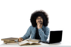 Afro student thinking an idea on studio. Afro male college student thinking an idea while studying with a laptop and textbooks on the desk Royalty Free Stock Photos