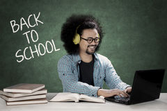 Afro student uses a laptop and hear music. Picture of an Afro college student is using a laptop and hearing a music while sitting with word of back to school on Royalty Free Stock Photos