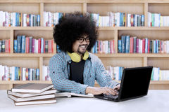 Afro student using a laptop in the library. Image of Afro college student is reading books while using a laptop in the library Stock Photo