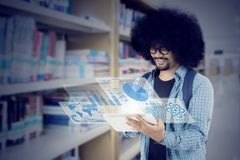 Afro student using tablet in the library. Image of Afro male student using a digital tablet with virtual screen and standing in the library Royalty Free Stock Photo