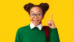 Free Afro Teenager Pointing Up Over Yellow Studio Wall Stock Photos - 169895553