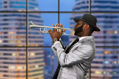 Afro trumpeter in black hat. stock photography