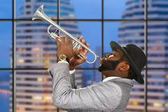 Afro trumpeter on city background. Stock Photo