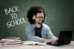Afro uczeń używa laptop i słucha muzykę Zdjęcia Royalty Free